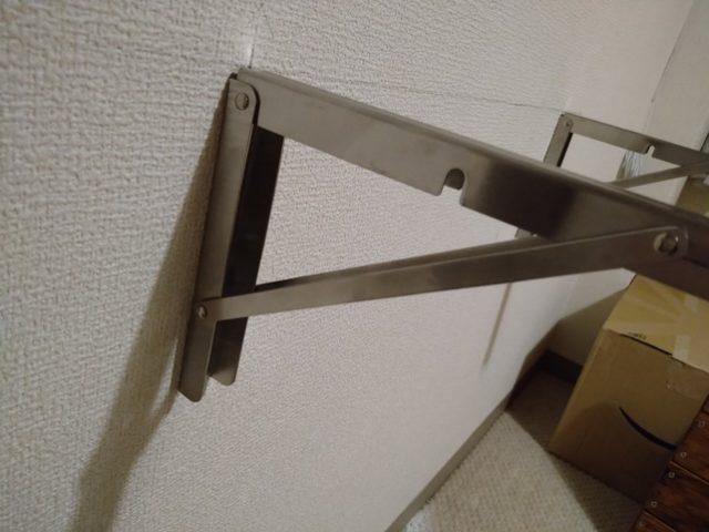 折りたたみ式棚受けを先に石膏ボードに取り付け